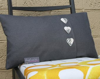 Charcoal grey linen cushion with heart-shaped ceramic buttons