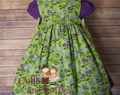 Eva's green and purple flowered pinafore.