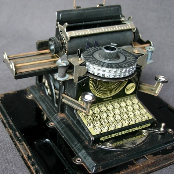 The Elegant black antique toy typewriter. Vintage collectible writing embossing portable tool.