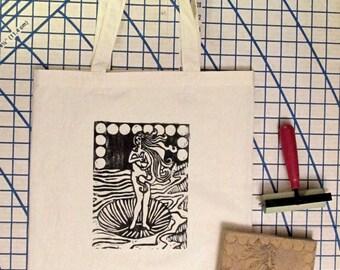 Tote Bag, Venus Breastfeeding, linoleum block print. Natural muslin bag with dark brown design. Normalize breastfeeding.