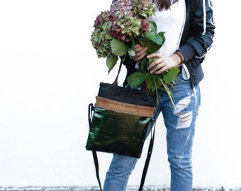 Foldover purse made of glossy dark green leather and black nappa leather that can be carried two ways: as a long tote or as a crossbody