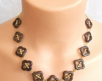 Brown marrocan open beads with 3 gold beads inside each.  This will definitely go with at least ONE of your tops!