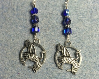 Silver flying crane charm dangle earrings adorned with dark blue Czech glass beads.