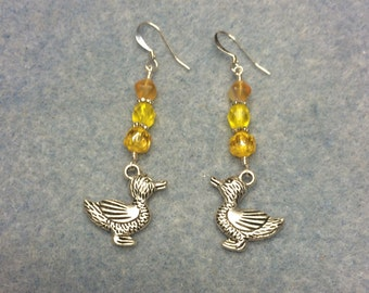 Silver duck charm dangle earrings adorned with yellow Czech glass beads.