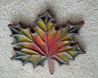"""Maple Leaf trivet/wall hanging Victoria Littlejohn ceramics. 9"""".7"""". 1/2 thick on cork base. Very good condition."""