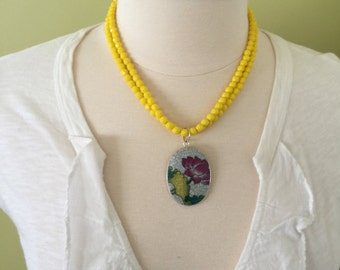 "Summer statement double strand of yellow faceted glass beads with colorful porcelain pendent, 20"" length."