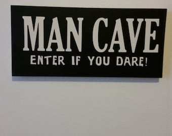 "Black ""Man cave: enter if you dare"" sign"