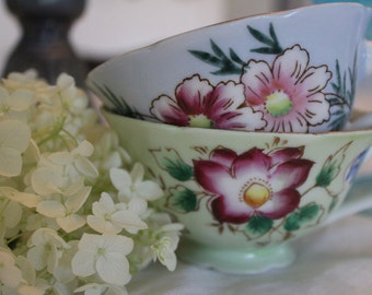 Set of two cups (one green and one blue) with floral pattern