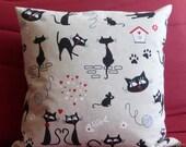 Housse de coussin en tissu, couleur beige, motifs chats noirs, fermée par zip