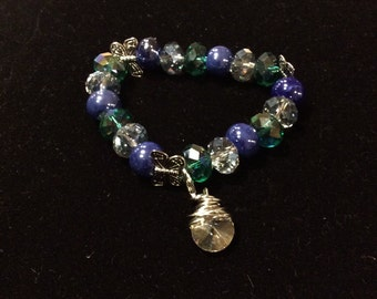 Crystal beaded bracelet with butterfly spacers and accent charm