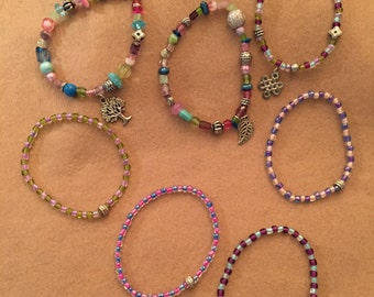7 nulti-colored beaded stretch bracelets w/charms (on 3)