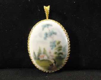 Porcelain Kaiser Pendant Country Scene Made in West Germany Oval Shaped Gold Accents Edging Green Grass Trees Blue Sky White Background