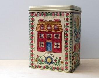 1970s Hallmark tin with folk art decorations. House and flowers.