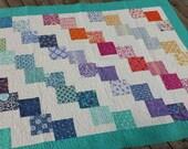 Modern rainbow quilt blanket teal cream pink blue gray orange falling charms Cuzco fabric