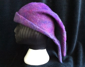 This most unusual hat is double layered in hand dyed and wet felted merino wool, it is deep teal, purple, green and deep rose