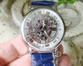 Silver on Silver See-Thru Looks Like Mechanical Skeletal Wrist Watch with Blue Leather-like Band Tiny Flower Charm A 372