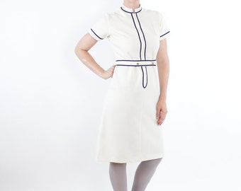 Vintage 60's polyester uniform dress, stewardess, waitress, pale yellow / off white, navy blue trim, belted, zip front - Medium