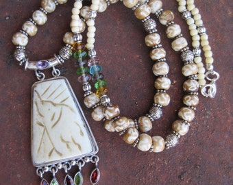 Carved Bone Boho Elephant Pendant with Garnet and Peridot Gem Drops on Long Necklace of Bone, Silver Tone Beads and Multi Colored Crystals