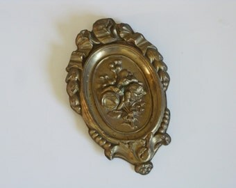 Gilded repousse metal gilded plaque with flowers and ribbons