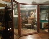 Antique tri-fold mahogany mirror with beaded trim.