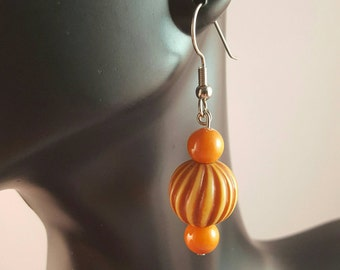 Brown and tan spiral bead dangle earrings accented with small round orange beads