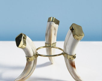 An imitation ivory tripod stand: Three elephant tusks are joined with a simple brass circle linked to bands around each tusk
