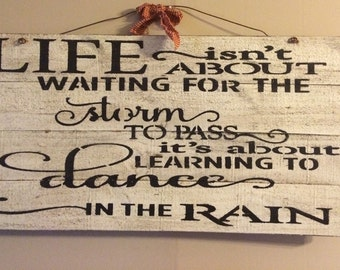 Large primitive sign: LIFE isn't about waiting for the storm to pass its about learning to dance in the rain