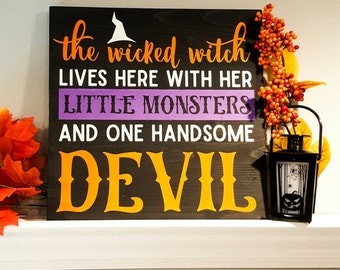 """The wicked witch lives here with her little monsters and one handsome devil, wood Halloween sign. 12""""x12"""". Black, orange, white and purple."""