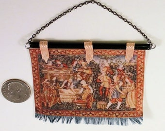 Colorful tapestry of Medieval or Tudor wine making, black rod, green fringe, pale coral ribbon. 1 to 12 scale miniature. Hand made in USA.