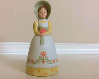 A Cute Small Country Girl Holding Flowers Figurine Bell, Avon.