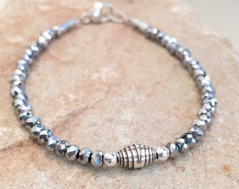 Sparkly gray bracelet made with glass rondelle beads, silver round beads, Hill Tribe silver rolled bead and tube beads with a lobster clasp.