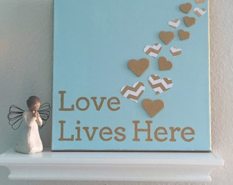 Love Lives Here - Gold and White on Light Blue canvas