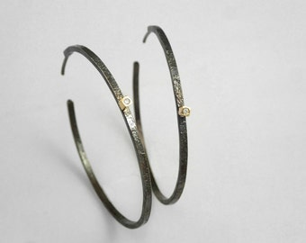 Hammered hoop earrings with diamond and rough surface. A classy piece of jewelry with personality.
