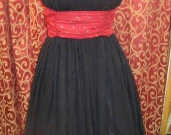 "1950's. 3 6"" bust, black silk ""cocktail dress""with gold dotted red cummerbund."