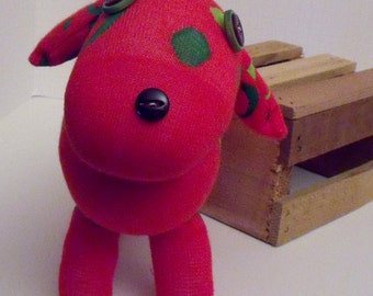 Sock Dog Made in the Style of a Dachshund Using a Red and Green Sock and Adorned With Red and Green Button Eyes and Button Nose With a Tail