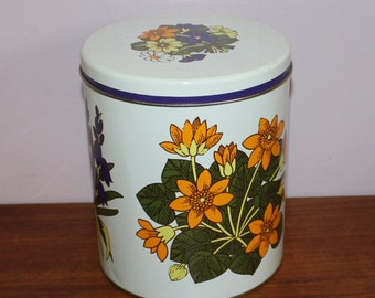 Lovely vintage 60s round tin canister with different retro flowers.