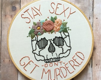 Stay Sexy Don't Get Murdered quote hand embroidery hoop art. Skull with flower crown. My Favorite Murder quote. 7 inch hoop.