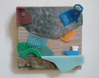 Small boat. Artworks made of waste, plastic soup washed ashore. Wooden panel, size 15 x 15 cm.