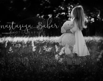Fine Art Photography Print in Black & White of a Small Girl in a Field of Wild Grass Holding a Stuffed Animal