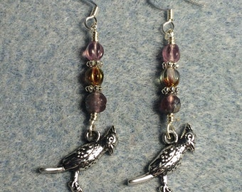 Silver cardinal charm dangle earrings adorned with small violet Czech glass beads.