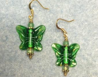 Emerald green lampwork butterfly bead earrings adorned with green Czech glass beads.