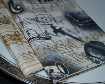 Set of 8 reversible cloth napkins that feature musical instruments and sheet music.