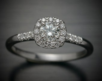 14kt white gold Diamond Engagement ring with a round center and cushion halo