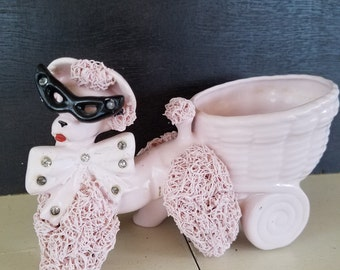 Vintage pink spaghetti poodle with cat eye glasses .