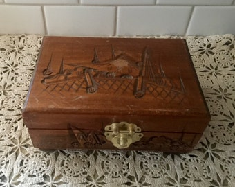 Carved wooden asian jewelry box with red interior