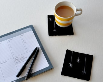 Black linen star coasters. Fabric coasters, machine-stitched quilted motif of star or icicle. Black white stripe on back. Housewarming gift