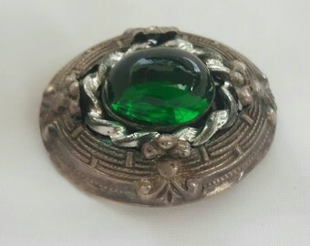 Antique pin with a green glass cab