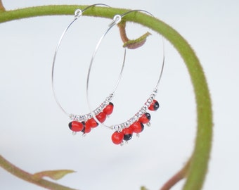 Large silver hoop earrings with huayruro seed beads