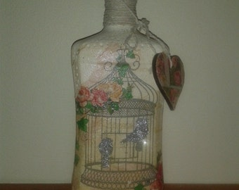 Beautiful vintage style upcycled glass bottle, addorned with glittered birds in cage, roses and script. Finished with string and heart