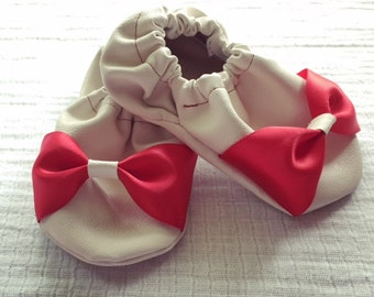 White leather shoe with red bow